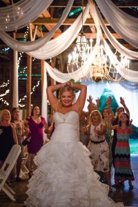 The bride throws the bouquet at the reception at The Barn at Fillauer Lakehouse.