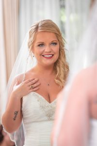 Bride smiles as she checks her makeup out in the mirror at Fillauer Lake house