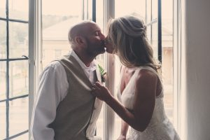 The bride and groom kissing by a window, by Kim Nix Photography one of the best wedding photographers in the Chattanooga tn area.