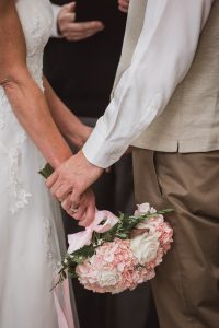 Couple holds hands during a ceremony at a Chattanooga wedding venue, photography by Kim Nix photography one of the best Chattanooga wedding photography companies in Chattanooga.